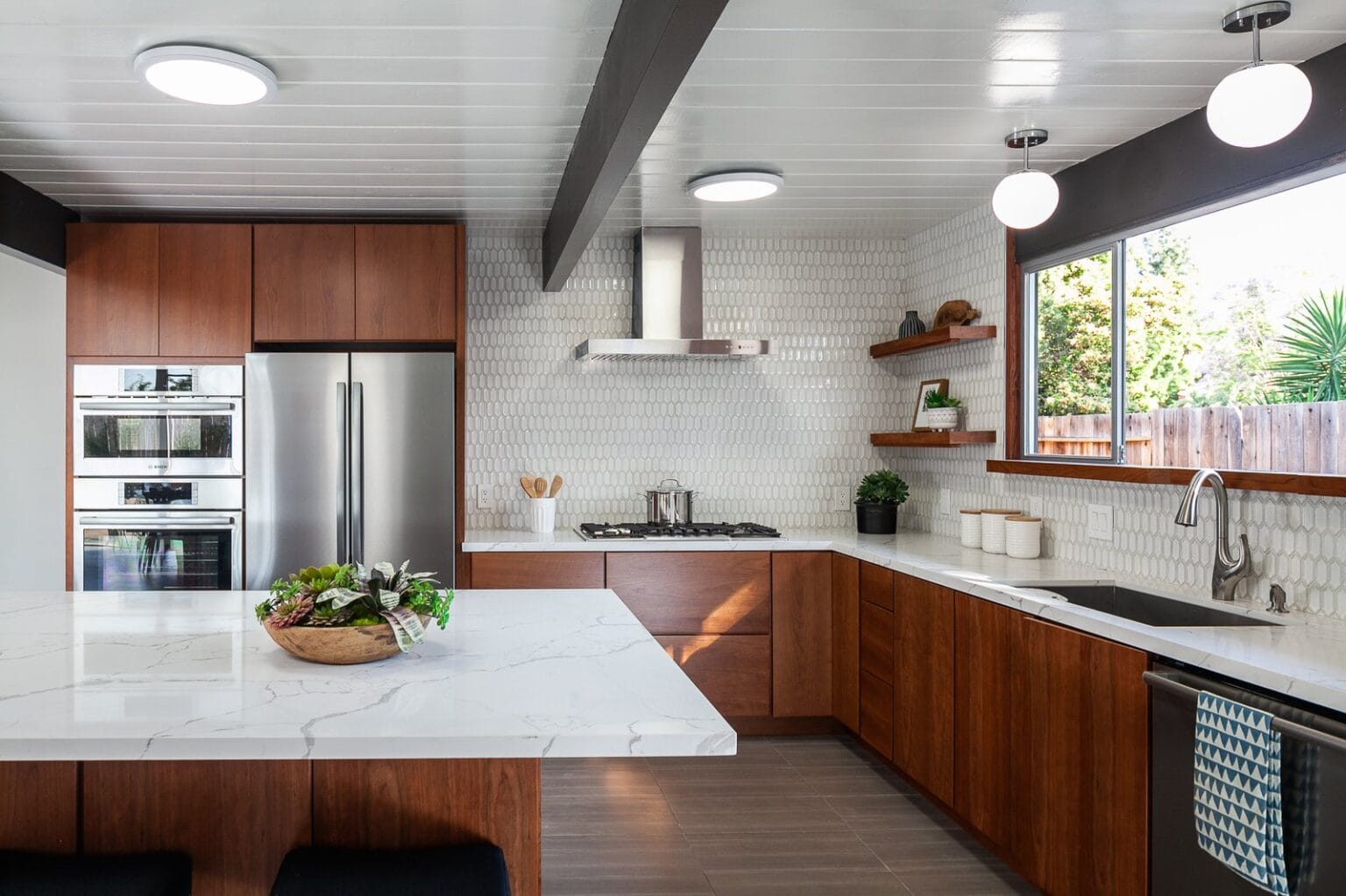 the-open-kitchen-is-bright-and-airy-with-updates-which-include-a-marble-topped-island-stainless-steel-appliances-and-a-stylish-tile-backsplash